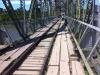 Auf dieser baufälligen Brücke überqueren die Fußgänger den Grenzfluß